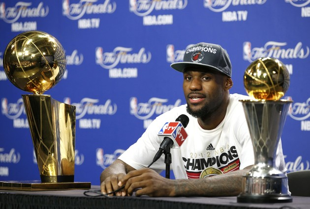 Miami Heat's James sits with the Larry O'Brien trophy and the NBA Finals MVP trophy after his team won the title by defeating the Oklahoma City Thunder in Game 5 of the NBA basketball finals in Miami